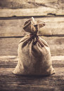 Grey tied sack on wood background Royalty Free Stock Photo