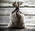Grey tied sack on wood background Royalty Free Stock Images