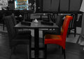 Greyscale restaurant interior with a red chair Royalty Free Stock Photo