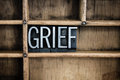 Grief concept metal letterpress word in drawer the written vintage type a wooden with dividers Royalty Free Stock Images