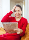 Grief mature woman with newspaper wonder at home Stock Photos