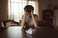 Grief stricken young woman with a crumpled letter on the table Royalty Free Stock Images