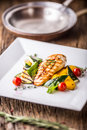 Grill chicken breast. Grilled vegetables with chicken breast. Grilled chicken with vegetables on oak table Royalty Free Stock Photo