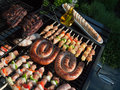 Grill food grilling on the bbq on a summer day boerewors skewers shashliks sausages herbs and vegetables Stock Photos