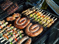 Grill food grilling on the bbq on a summer day boerewors skewers shashliks sausages herbs and vegetables Royalty Free Stock Photos