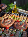 Grill food grilling on the bbq on a summer day boerewors skewers shashliks sausages herbs and vegetables Stock Photography