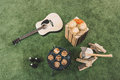 Grill with meat, hamburgers on wooden board, beer bottles and guitar on grass Royalty Free Stock Photo