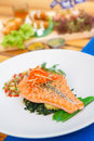 Grill Salmon Steak on the bed of Spinach in white plate Royalty Free Stock Photo