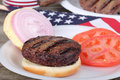 Grilled american burger hamburger with onion and tomato on a bun Royalty Free Stock Images