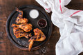 Grilled bbq chicken meat wings and legs served on round wood chopping board with two sauces and salt on white kitchen towel over Royalty Free Stock Images