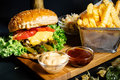 grilled beef burger with fresh vegetables and french fries served hot at local bistro Royalty Free Stock Photo