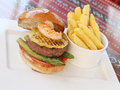 Grilled beef and seafood burger with pineapple asparagus tomato french fries surf turf Royalty Free Stock Image