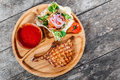 Grilled beef steak on bone, fresh salad, grilled vegetables and tomato sauce on cutting board on wooden background Royalty Free Stock Photo