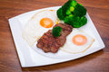 Grilled beef steak with eggs and broccoli Stock Photo