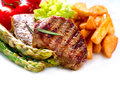 Grilled beef steak meat fried potato asparagus tomatoes Royalty Free Stock Images