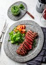 Grilled beef steak medium rare slices on gray stone plate with salad and chimichurri sauce Royalty Free Stock Photo