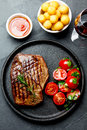 Grilled beef steak served on cast iron plate with tomato salad, potatoes balls and red wine. Barbecue, bbq meat beef Royalty Free Stock Photo