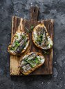 Grilled bread sardines micro greens sandwiches on a rustic cutting board on a dark background, top view