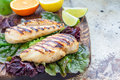 Grilled chicken breast in citrus marinade on salad leaves and wooden board, horizontal, copy space Royalty Free Stock Photo