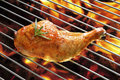 Grilled chicken thigh on the flaming grill Royalty Free Stock Images