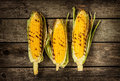 Grilled corn cobs on vintage wood background rural kitchen Stock Photo