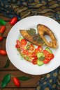 Grilled fish steak with vegetables on plate: tomatoes, microgran, cucumber, tasty and healthy dinner. Wooden rustic background. To Royalty Free Stock Photo