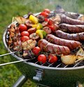 Grilled food. Various grilled products: Grilled sausages, meat and vegetable skewers, bacon and vegetables on the grill plate, out Royalty Free Stock Photo