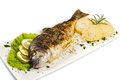 Grilled gilt head sea bream on plate with lemon and rosemary and