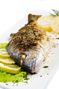Grilled gilt head sea bream on plate with lemon and rosemary and potatoes Stock Photos