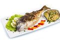 Grilled gilt head sea bream on plate with lemon salad and grill vegetables Stock Photos