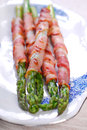 Grilled green asparagus wrapped in bacon slices Stock Photo