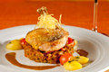 Grilled guinea fowl fried on red lentils with red and yellow cherry tomatoes and potatoes decorated with thyme and crispy potato Stock Images