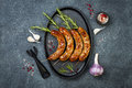 Grilled homemade rosemary sausages skewers on iron frying pan over rustic dark stone kitchen table. Top view, flat lay. Royalty Free Stock Photo