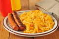 Grilled hot dogs with mac and cheese macaroni on a rustic wooden table Stock Photos