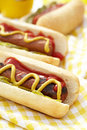 Grilled hot dogs with mustard ketchup and relish on a picnic table Stock Photography