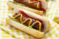 Grilled hot dogs with mustard ketchup and relish on a picnic table Royalty Free Stock Photo