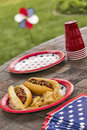 Grilled hotdogs at a patriotic holiday bbq american cookout with that are topped with ketchup and mustard and are served with Royalty Free Stock Photo