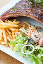 Grilled juicy barbecue pork ribs in a white plate with fries salad and parsley Stock Photo