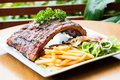 Grilled juicy barbecue pork ribs in a white plate with fries salad and parsley Stock Image