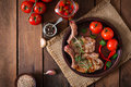 Grilled juicy steak on the bone with vegetables on a wooden background. Royalty Free Stock Photo