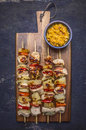 Grilled kebabs with peppers, pork and pineapple on a cutting board with sauce on wooden rustic background top view close up Royalty Free Stock Photo