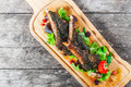 Grilled lamb ribs in herbs and greens, fresh salad, grilled vegetables and berries on cutting board on wooden background