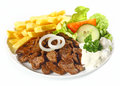 Grilled lean beef nuggets called dönerteller or doner doenerteller served with oven baked potato chips and fresh healthy salads Royalty Free Stock Images