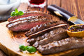 Grilled marinated flank steak well done beef on wooden board Stock Photo
