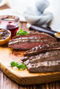 Grilled marinated flank steak well done beef on wooden board Royalty Free Stock Images