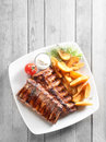 Grilled Meat, Fried Potatoes with Sauce on Plate Royalty Free Stock Photo