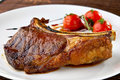 Grilled meat ribs on white plate with tomatoes Stock Photo