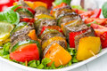 Grilled meat on skewers with vegetables on salad leaves Stock Images