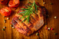 Grilled meat on wooden plate closeup detail of steak with spices and rosemary a Royalty Free Stock Photo