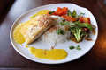 Grilled pacific halibut filet with toasted coconut and a mango aioli served with rice and vegetables Royalty Free Stock Photo